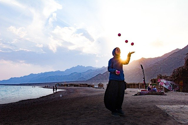 A woman juggling four balls in a mountainous region