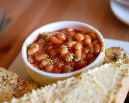 Baked beans in a ramekin near some toast