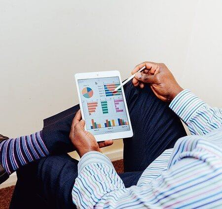 A man pointing at a spreadsheet on his device wearing bright socks with shoes