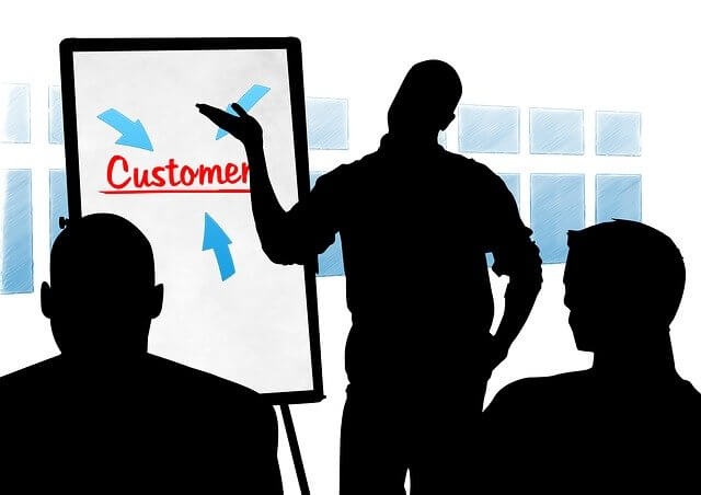 Businessmen discussing customers around a customer chart