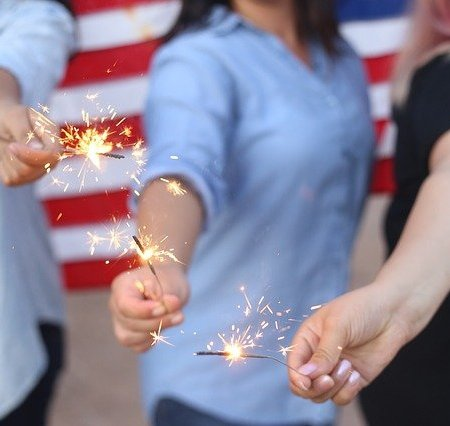 Employees holding indoor sparklers near the American flag