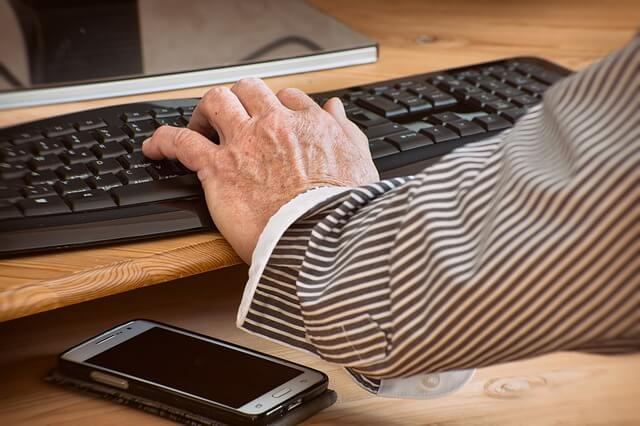 One hand typing on a keyboard whilst the other hand drums on the desk