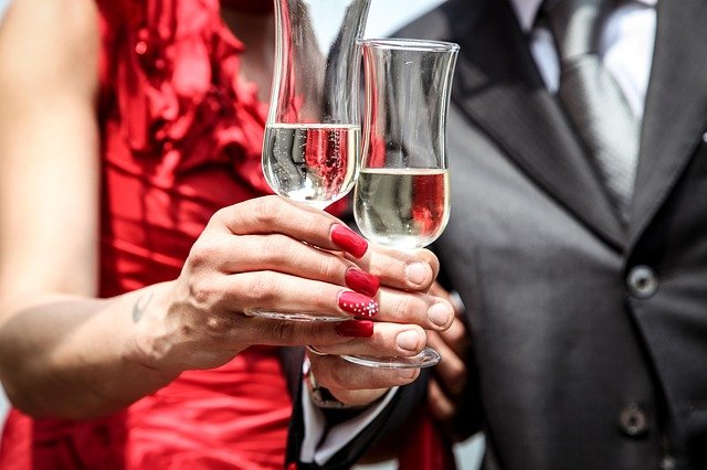 A dressed up couple holding champagne glasses at an event