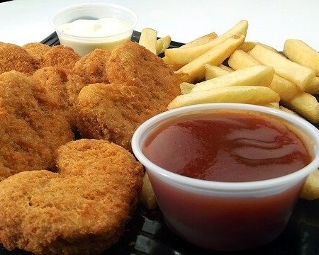 Chicken nuggets with a small ramekin of BBQ sauce