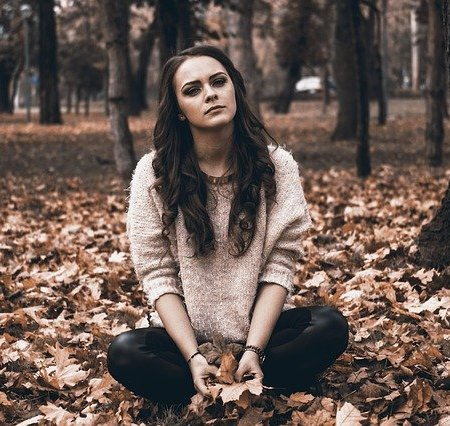 An upset girlfriend sitting on some autumn leaves