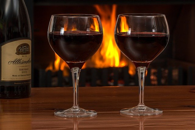 Two glasses of red wine near to a fireplace